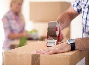 .Close up of male hand packing cardboard box, concept moving house