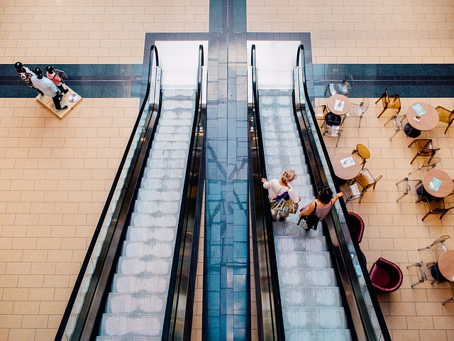 escalators and cafe tables inside a mall