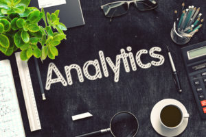the word analytics written on a black chalk board surrounded by office supplies such as coffee cup glasses and other office paraphernalia