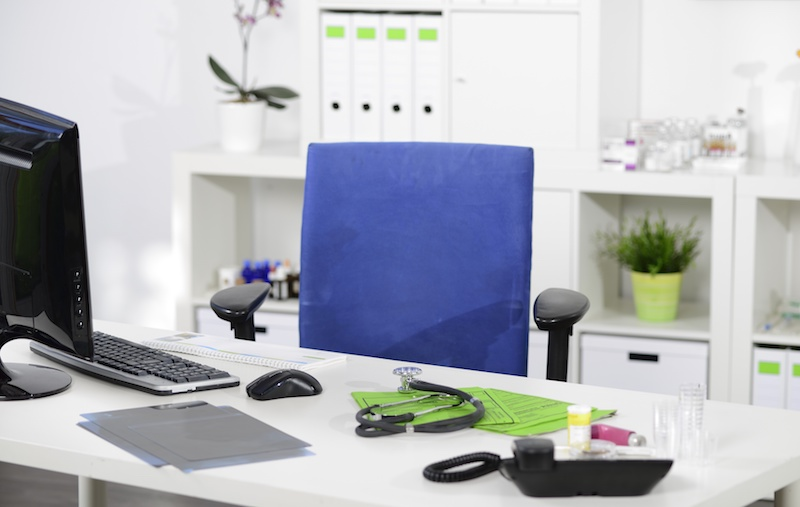 desk with a stethoscope on it in a medical office with blue desk chair