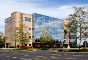 a modern commercial office with big glass windows situated in the middle of a parking lot
