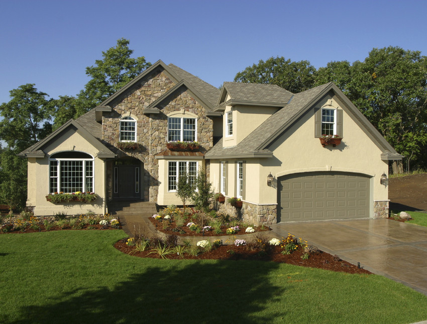 newly constructed home exterior with beautiful stone and landscaping